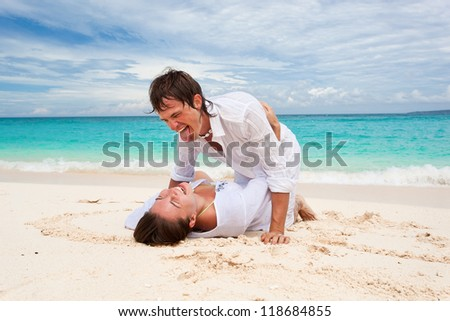 Lovely laughing couple on beach - stock photo
