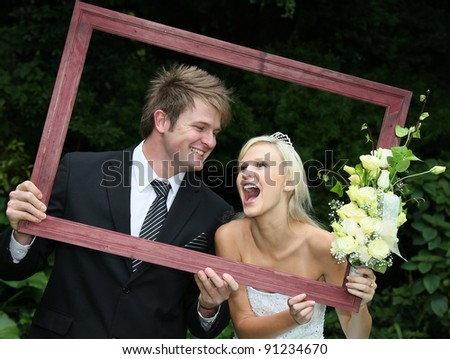 Lovely laughing wedding couple looking through a wooden picture frame - stock photo