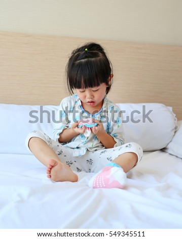 Lovely little asian girl trying to put a socks on the bed.