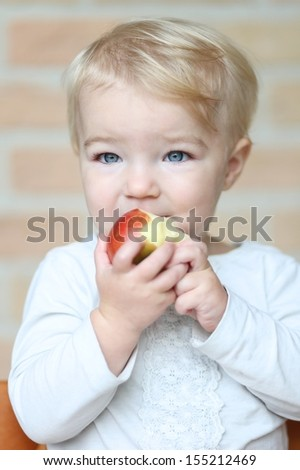 Lovely little blond baby girl bites on tasty red apple - stock photo