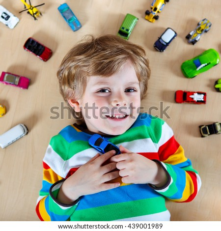 Lovely Little blond child playing with lots of toy cars indoor. Kid boy wearing colorful shirt. Happy preschool child having fun at home or nursery. - stock photo