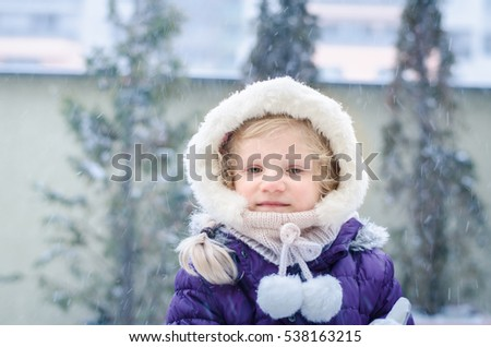 lovely little blond girl playing with snow