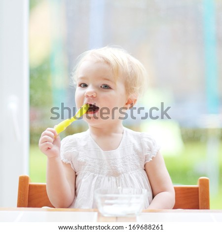Lovely little blonde toddler girl eating delicious yogurt sitting in the kitchen in a high feeding chair next to a big window with garden view