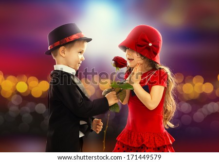 Lovely little boy giving a rose to fashionable girl and her excited - stock photo