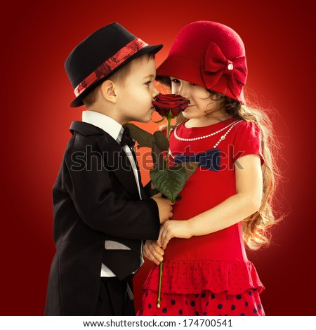 Lovely little boy giving a rose to fashionable girl and her excited. Love concept - stock photo