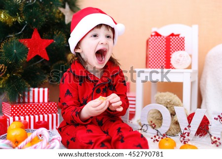 Lovely little boy in Santa hat with tangerine sits near Christmas tree - stock photo