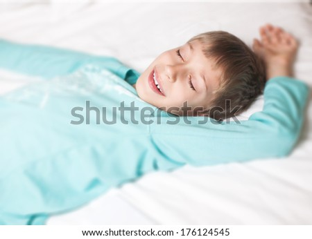Lovely little boy peacefully sleeping in a bed smiling seeing a dream - stock photo
