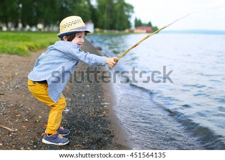 lovely little boy plays with stick on riverside