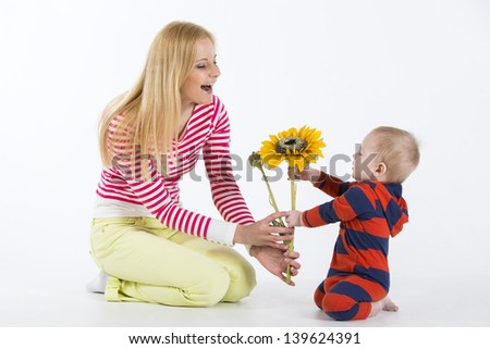 Lovely little boy sitting on knees in studio and giving sunflower to his mother.