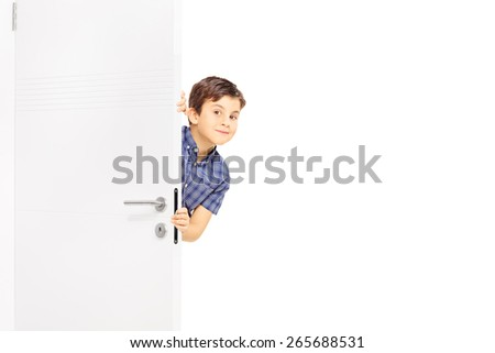 Lovely little boy sneaking a peek behind a door and looking at the camera isolated on white background - stock photo