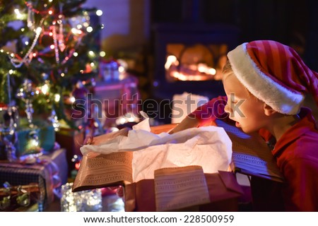Lovely little boy with a santa claus hat opens a gift in front of the Christmas tree lit up, in the warm atmosphere of Christmas,  a wood stove in the background - stock photo