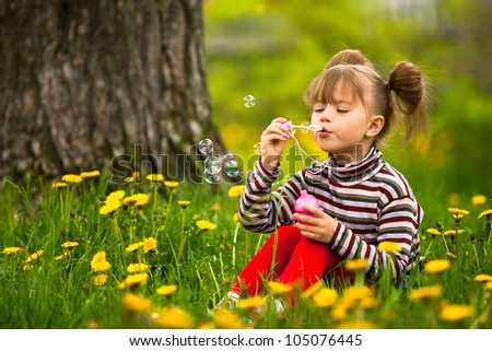 Lovely little five-year girl blowing soap bubbles in the park