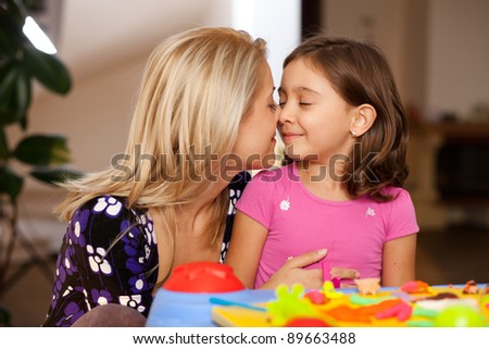 lovely little girl and her mother cuddling after playing - stock photo