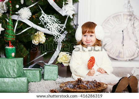 Lovely little girl eating a lollipop. Portrait of a funny little baby girl in earmuffs with a delicious candy in the hands. Christmas and New Year concept - stock photo