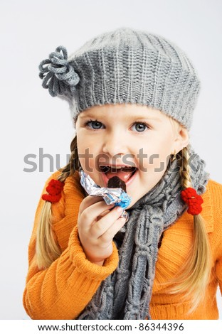 Lovely little girl eating chocolate candy - stock photo