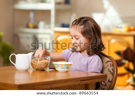 lovely little girl having breakfast: grabbing cereals from the bowl - stock photo