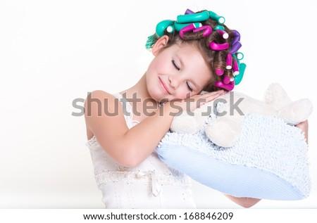 Lovely little girl in pajamas sleeping on pillow in hair curlers, glamour child,bedtime. Funny little girl portrait. isolated on white background, studio.  - stock photo