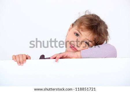 Lovely little girl leaning on a white panel - stock photo