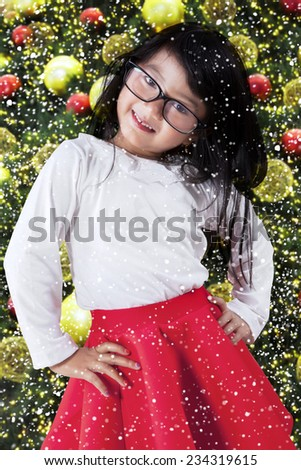 Lovely little girl looking at the camera while posing near christmas tree at home - stock photo
