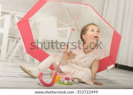 Lovely little girl playing tea party sitting under an umbrella, indoor shot in white room - stock photo