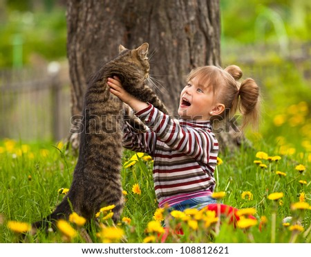 Lovely little girl playing with a cat. - stock photo