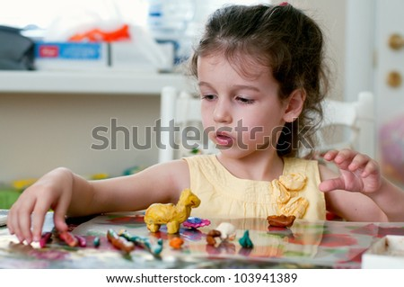 Lovely little girl playing with plasticine in her room - stock photo