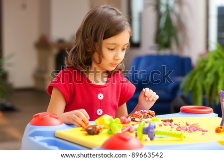 lovely little girl playing with plasticine on her playtable - stock photo