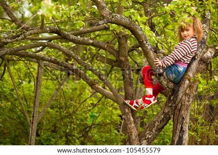 Lovely little girl posing sitting on a tree in the garden - stock photo