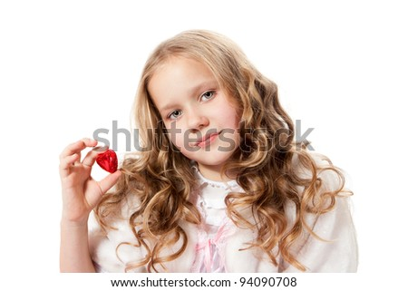 Lovely little girl showing chocolate heart-shaped candy - stock photo