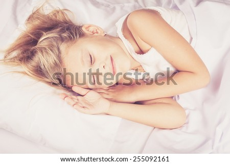 Lovely little girl sleeping on the bed at home - stock photo
