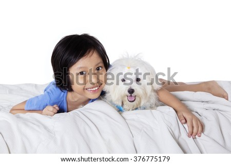 Lovely little girl smiling happy while looking at the camera with her dog on bed, isolated on white background - stock photo