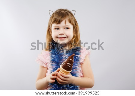 Lovely little girl wearing pink dress, metal cat ears and blue festoon holding an ice-cream, looking right at gray studio background, copy space. - stock photo