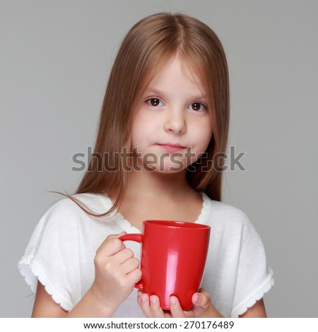 Lovely little girl with a cup of hot tea on gray background - stock photo