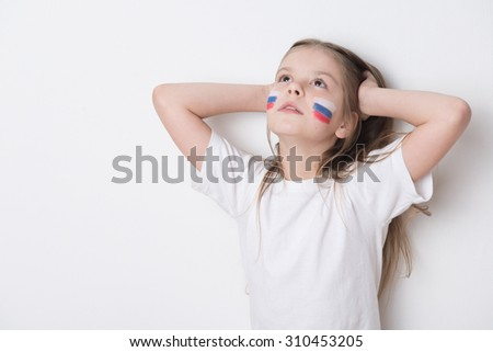 Lovely little girl with a Russian flag painted on her face - stock photo