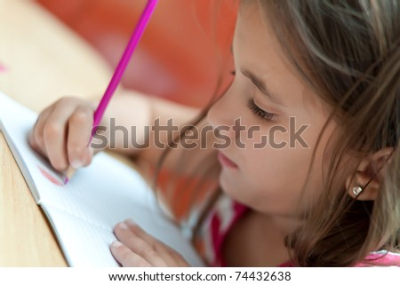 Lovely little girl working in her school project at home - stock photo