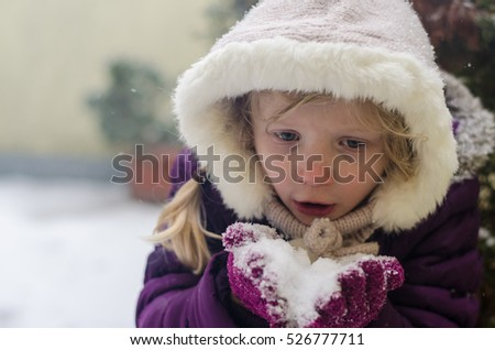 lovely little kid playing with snow