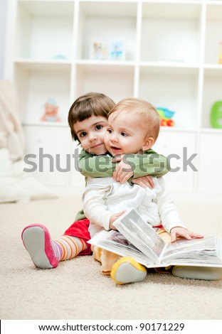 Lovely little sister hugging her baby brother - stock photo