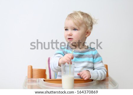 Lovely little toddler girl in blue stripes sweater drinking milk from the glass with straw sitting indoors in high feeding chair against the while wall - stock photo