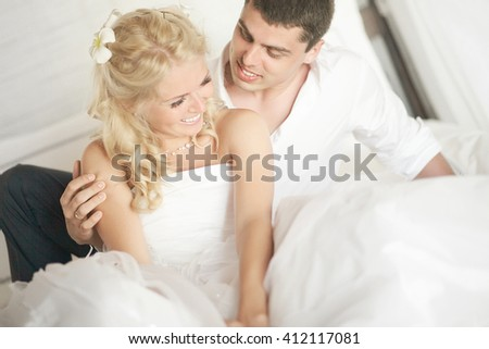 Lovely married couple teasing each other lying on bed. Playing with fruits, joking and enjoying wedding day. - stock photo