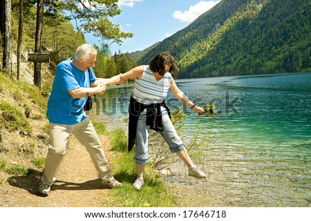 lovely mature couple hiking beside a lake - stock photo