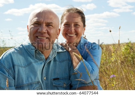 Lovely mature couple poising against summer landscape - stock photo