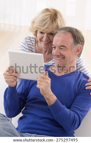 lovely mature couple using tablet computer at home - stock photo