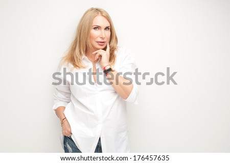 Lovely mature woman in white shirt and blue jeans - stock photo