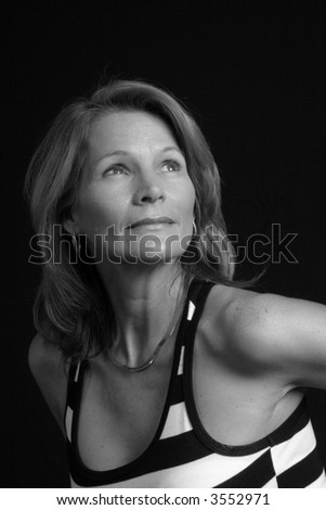 Lovely mature woman looking up and left in black and white.