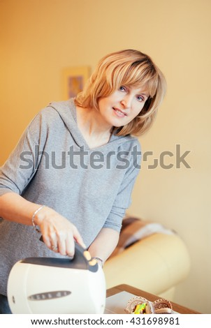 Lovely middle-aged blond woman with a beaming smile sitting at home having tea