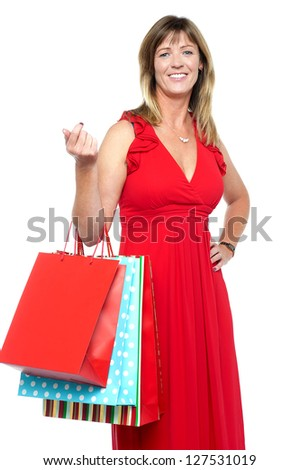 Lovely middle aged lady striking stylish pose with vibrant colored shopping bags. - stock photo
