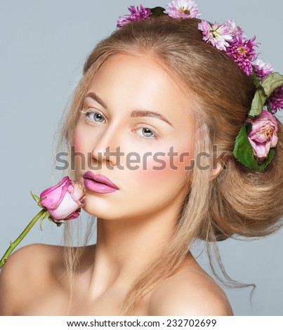 Lovely model with shiny volume curly hair with flowers, winter white eyelashes make-up, vivid lips and pink cheeks. Christmas look - stock photo