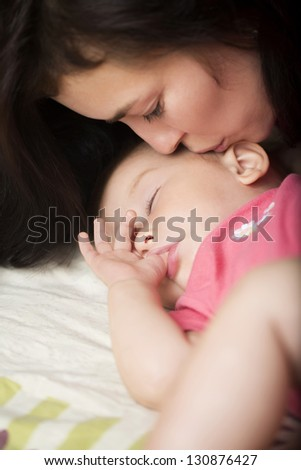 Lovely mother with her little daughter sleeping in bed