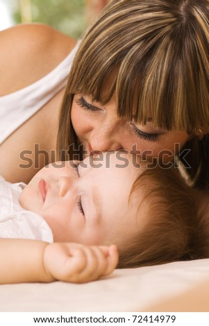 Lovely mother with her little daughter sleeping in bed - stock photo