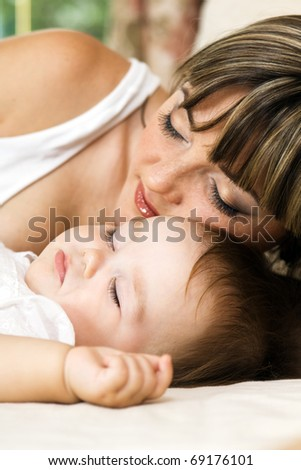 Lovely mother with her little daughter sleeping in the bed - stock photo